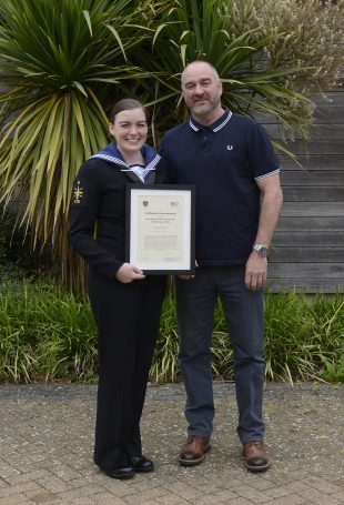 A picture showing ET Chelcie Evans holding her framed ISS Chief Executive Officer's commendation, alongside her Father