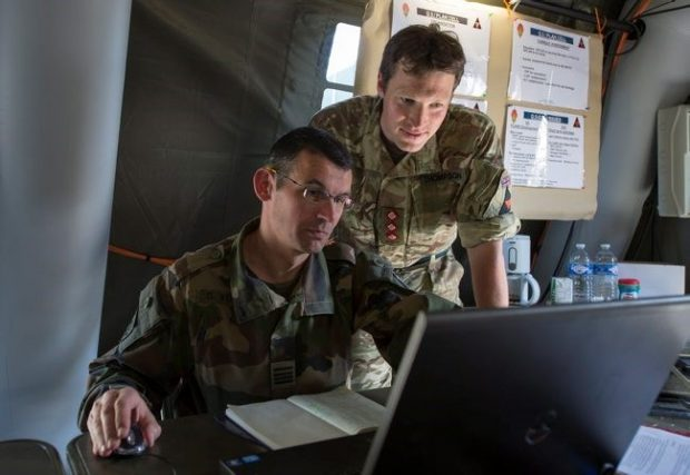 Two male service personnel looking at a laptop screen