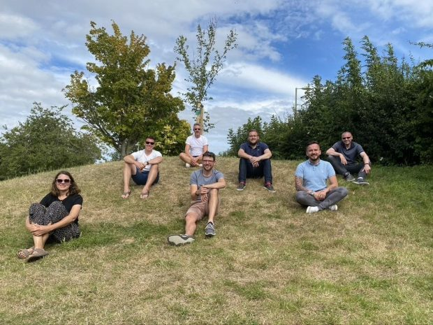 A photograph showing 7 members of the R2-D2 team sat on the grass in a socially distanced manner.