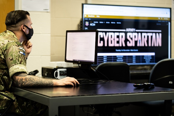 An image showing a military person working at a computer. A screen in the background shows the words 'Cyber Spartan'